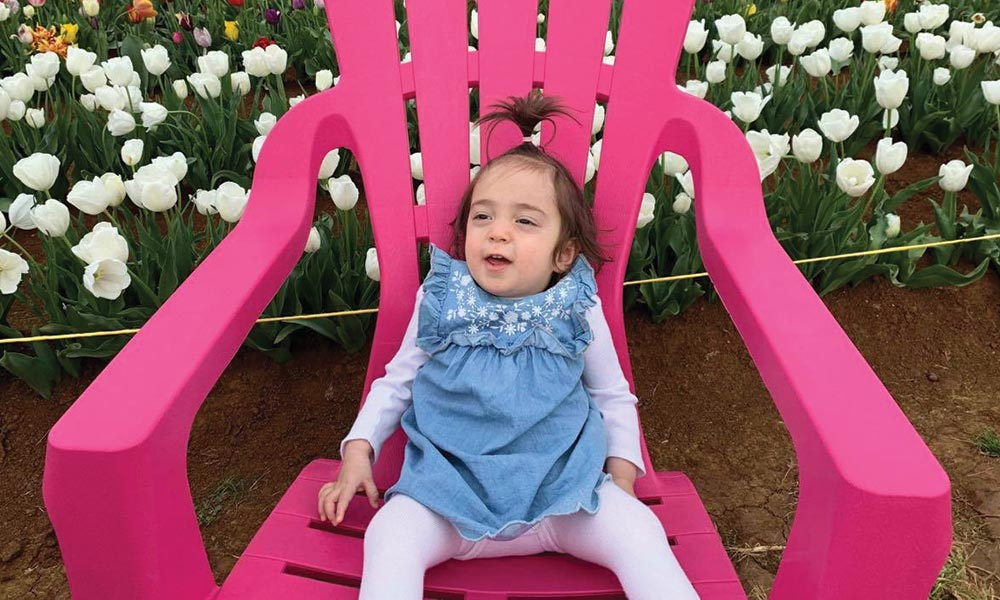 Poppy seated in a giant pink chair outdoors amoung flowers