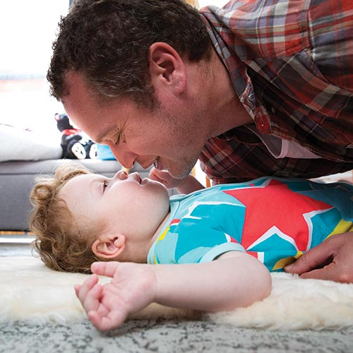 Marc with his son Sebby, playing on the floor